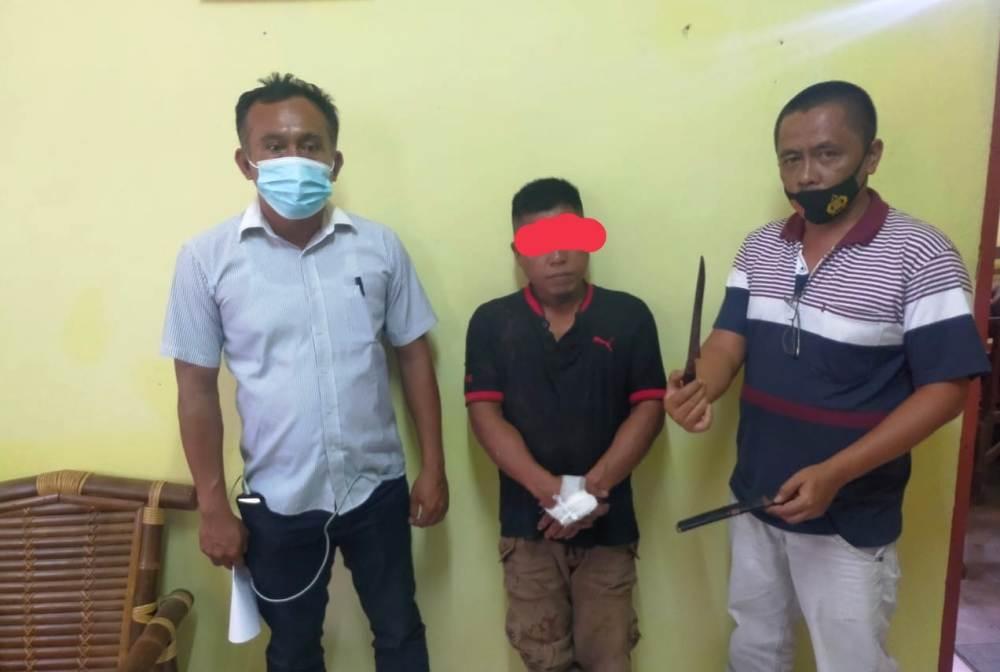 Petugas Kepolisian Sektor Tigalingga mengamankan EKG (tengah) tersangka pembunuhan teman sekampung Kiranta padang, beserta barang bukti berupa sebilah pisau tumbuk lada, Kamis (1062021). (istimewa)